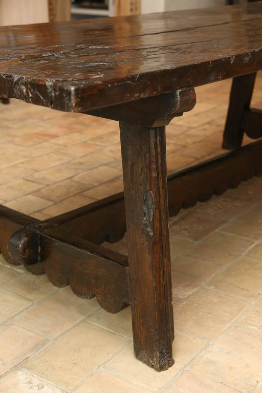 18th century thick slab walnut table with a two board top. The base is a 100 years old. Table is from the Abuzzo region of Italy. Both the legs and the trestle have a hand-carved scallop detail a variation on the St. Antonio style.