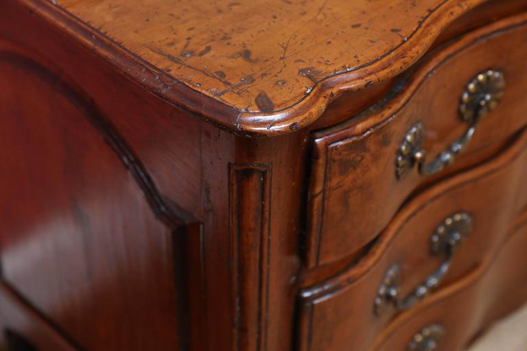 Spectacular 18th century walnut commode with three drawers and original hardware. Each drawer follows the lines of the top of the piece and have been carved out of a single piece of wood to produce the wavy pattern seen.