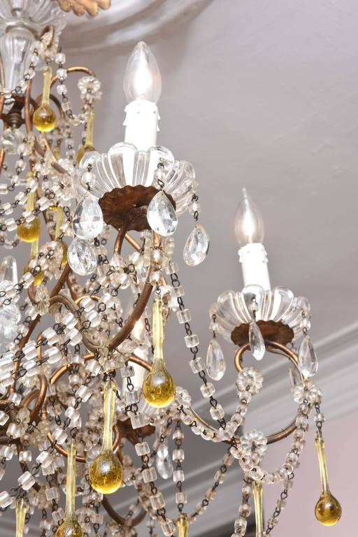 A charming blown glass bead swag chandelier with amber colored drops. Retaining its all original glass pieces and we do not see any florettes missing. Beautifully proportioned and as you can see in working order. Nice patina to the gilt metal and