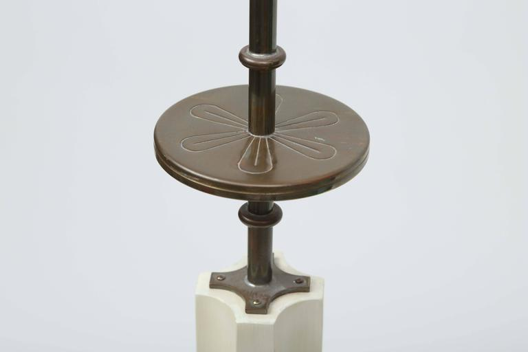 Original laquer finish and patinated hardware add to the elegance of these floor lamps.