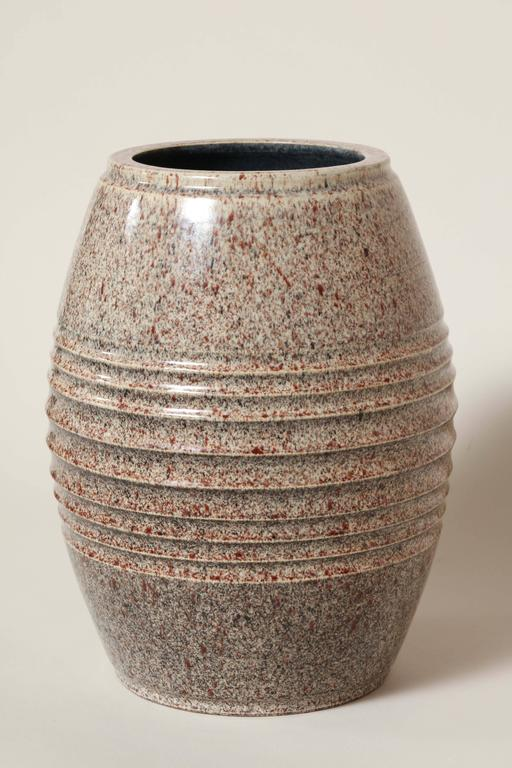 Designed by Willy Wuilleumier. Executed by Marcel Guillard. Produced by Editions Etling.  Heavy ovoid vase with ecru ground speckled with red and black and nine circular indentions around middle. Impressed Wuilleumier scp/Marcel Guillard/ France/