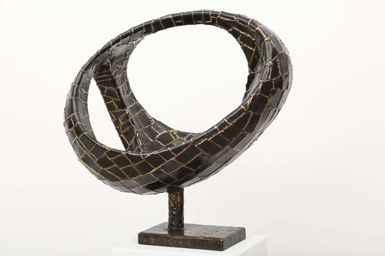 Abstract sphere sculpture in bronze, with three oval openings. Coming from the inside bottom of the piece and becoming more narrow towards the top.   The ovoide shape gives a cosmic aspect to this abstract piece. Unic and signed piece. The base is