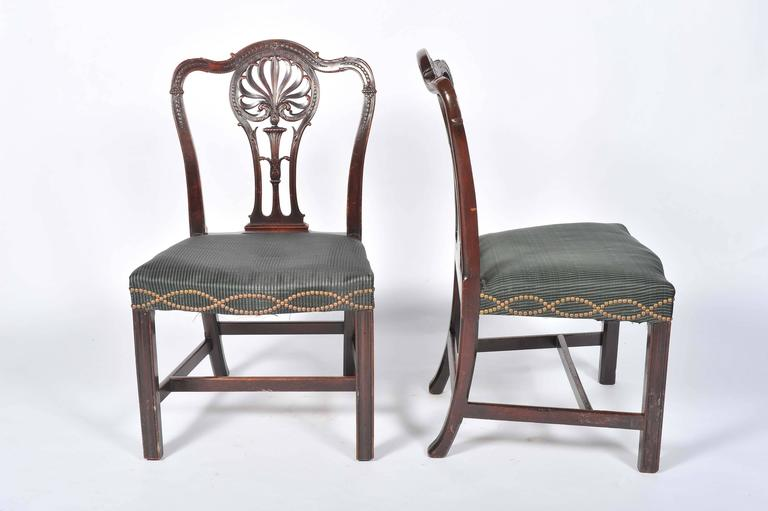 A good quality pair of Adam influenced side chairs having carved foliate decoration to the splats. serpentine shaped seat with close nail upholstery, raised on a square section moulded leg.