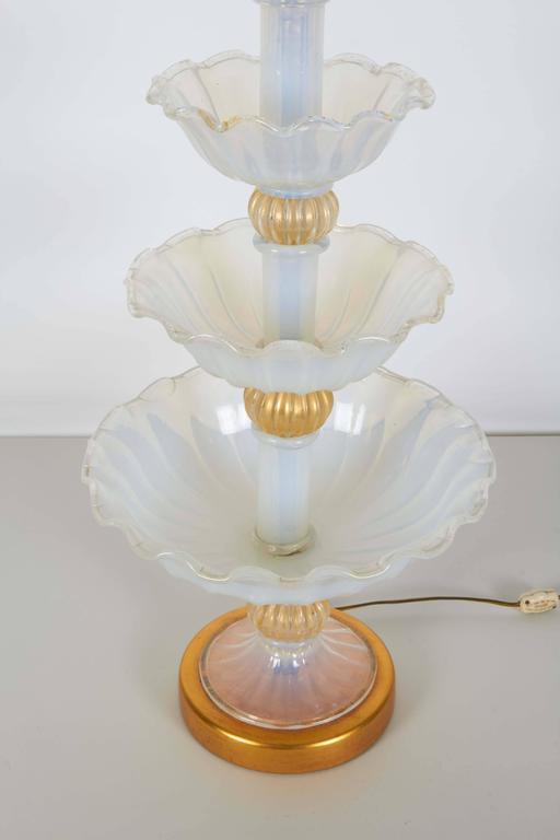 An impressive table lamp in opalescent Murano glass by Seguso, manufactured circa 1950s, with three graduated levels of handblown bowls with ruffled edges, accented with four gold leaf ribbed bulbs, on circular gilt metal base. Wiring and double