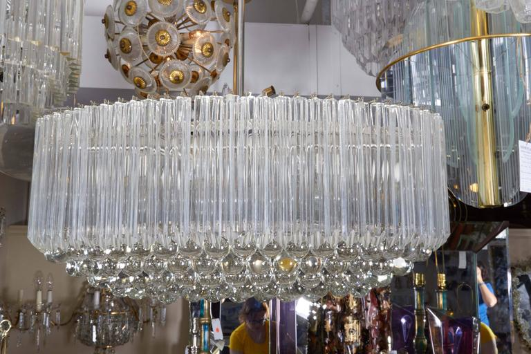 An Italian circa 1970s chandelier by Venini, with quatro punta Murano glass prisms and crystal balls suspended from a metal oval frame. Very good vintage condition, wear to metal and minor presence of chips to glass, consistent with age and
