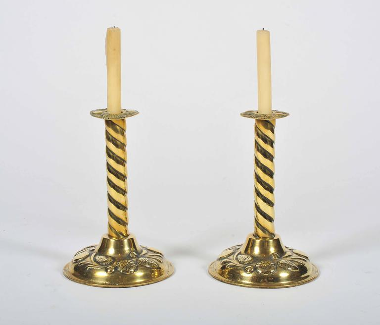 A most unusual pair of 19th century brass candlesticks. The stems of barley twist design, the pressed rims and cast bell shaped bases with fine foliate and floral decoration.