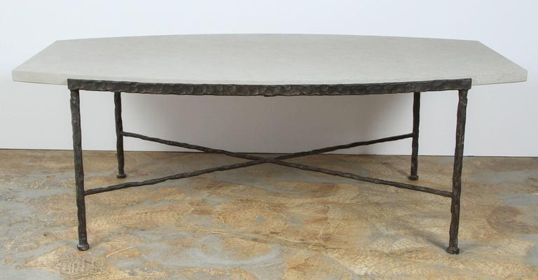 Paul Marra Ellipse cocktail table in textured iron and bateig blue stone. Bowed shape, hand-hammered, Giacometti vibe. By order.