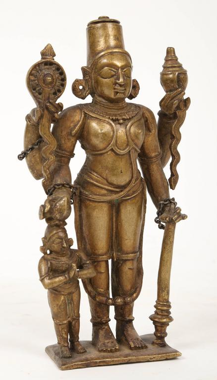A four-armed depiction of the Lord Vishnu holding the discus and the conch in the rear hands of the upraised arms. The deity wears a high crown and has earrings and bracelets. A long heavy dhoti falls from the belt below the slender waist almost to