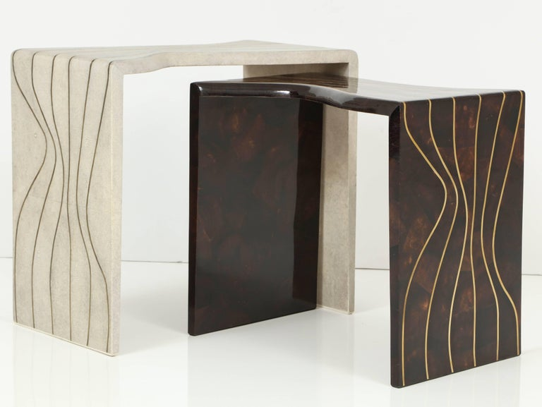 Beautifully designed nesting tables in shagreen and sea shell with brass inlays. An organic style with curvy design and edges. The design looks like a storm, France. The shagreen table measure: L 23.5, W 14, H 21.5. The sea shell table measure: L