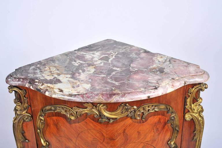 A good quality French, 19th century, kingwood marquetry inlaid corner cabinet, having its original Breccia marble top, the inlaid decoration of flowers and gilded ormolu mounts. The bombe fronted door opening to reveal a shelf within and raised on
