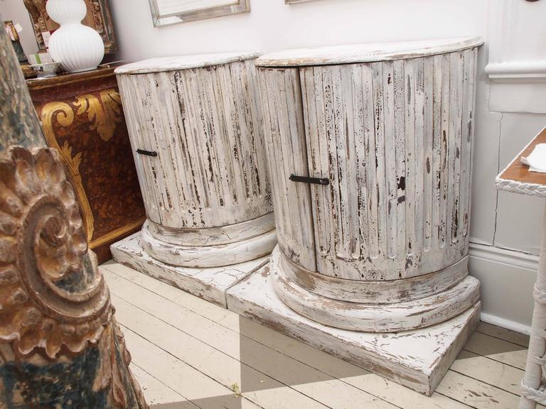 Pair of wood carved and painted column cabinets. Gorgeous patina. Unique design. Measures: Base 34 w x 16.5 deep.