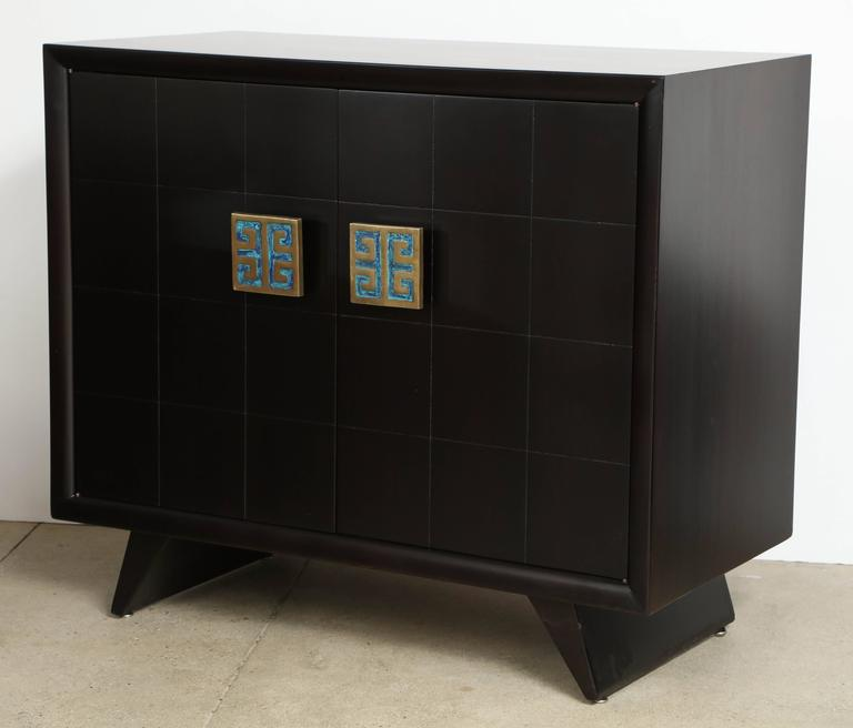 Pair of matte finished ebonized mahogany cabinets by Grosfeld House of New York with large Pepe Mendoza bronze pulls with blue and green enamel. Cabinets have two doors which conceal four pull-out drawers. Mint restored.