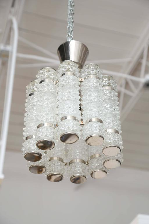 Orrefors chrome and crystal round pendant fixture By Tyringe Crafts. 10 faceted crystal cylinders attached by chrome curved supports and chrome caps top and bottom. Takes one standard Edison light bulb 60 watt max  in centre.  Has been rewired to