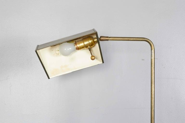 A brass circa 1960s pharmacy floor lamp, tent form shade with trimmed border and white enamel interior, on adjustable curved stem and round base. Good vintage condition, with age appropriate patina and wear to enamel interior, scratch to base.