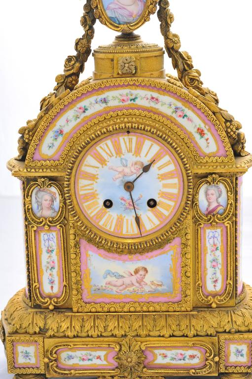 A very pretty 19th century French pink 'Sevres' porcelain and gilded ormolu mantel clock. Having classical foliate and swag decoration surrounding the pink porcelain plaques which depict classical women, cherubs and flowers. The porcelain face with