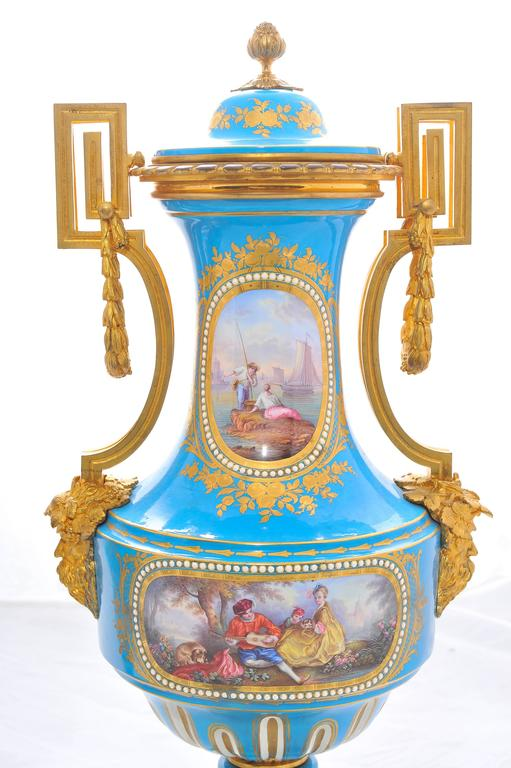 A very good quality pair of 19th century lidded 'Sevres' porcelain lidded vases. Each having wonderful gilded ormolu mounts. Classical hand-painted scenes set on a Turquoise back ground with golf leaf and raised on ormolu bases.