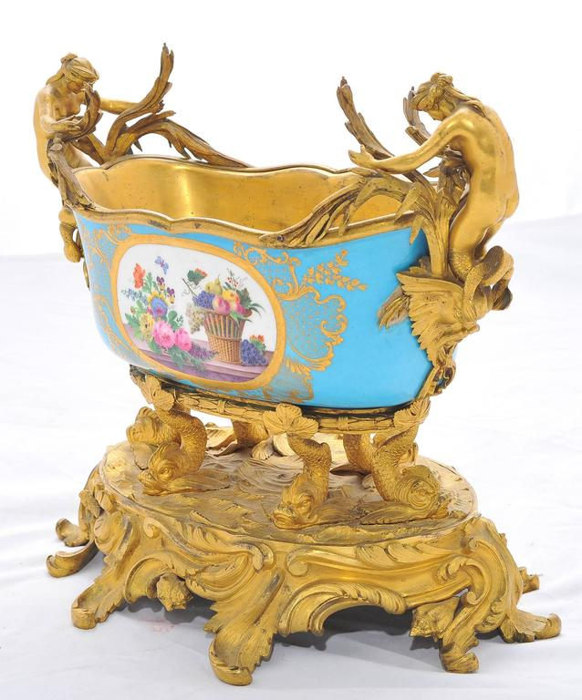 A very impressive 19th century gilded ormolu and French 'Sevres' porcelain jardiniere. Having mermaids and dolphins supporting the turquoise coloured bowl which has floral inset painted panels and raised on a 'C' scrolling ormolu base.