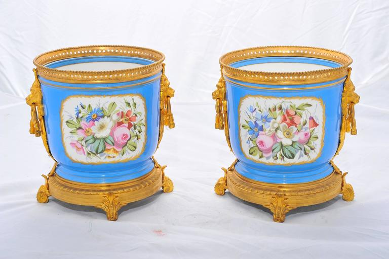 A good quality pair of French 'Sevres' porcelain jardinières, having classical romantic scenes to the front and floral scenes to the reverse.