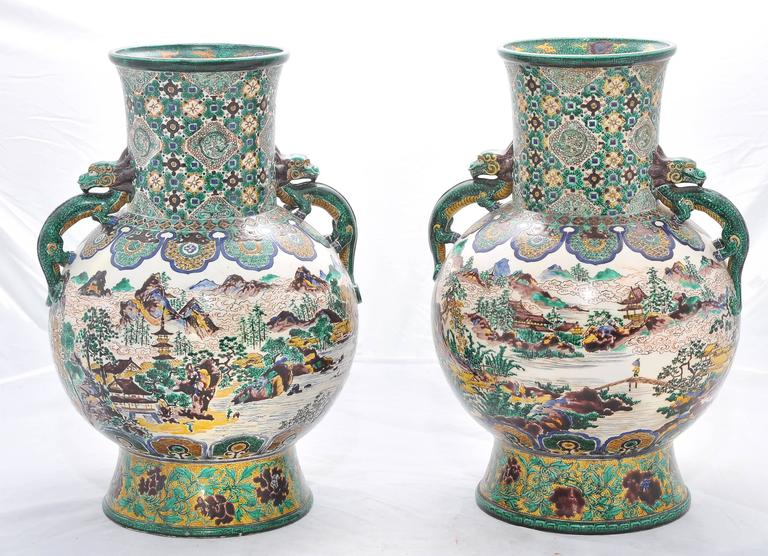 A large and decorative pair of 19th century Japanese Kutani vases. Having an unusual Green background with classical symbols and motifs. Mythical creators as handles. The central scene depicting lakes, mountains and pagoda topped buildings.