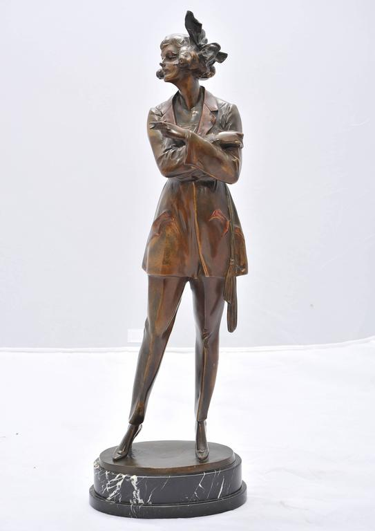 A wonderful modelled bronze statute by Bruno Zach, of a stylish young lady of the 1920s in dressed in a trouser suit and smoking a cigarette, signed to the base and mounted on a portoro marble base.