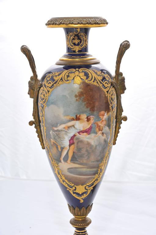 A good quality pair of 19th century 'Sevres' porcelain hand-painted classical vases, depicting romantic scenes to the panels, set in a dark blue background with gilded decoration and raised on ormolu bases.