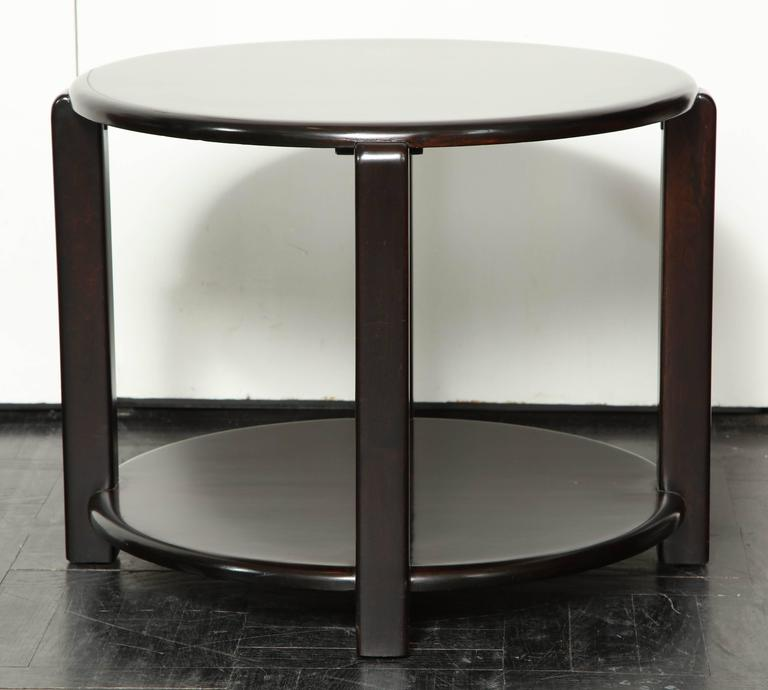 Mid-20th century two-tier ebonized walnut circular table, four polished supports.