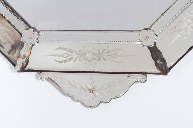 A Venetian wall mirror in the Hollywood Regency manner, with an elaborately detailed octagonal frame, decorated with frosted and convex floral designs and rosettes, surmounted by scrolling acanthus leaves. Overall good vintage condition, with age