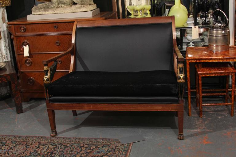 Egyptian Empire style small sofa/settee with carved wood winged sphinx armrests upholstered in black velvet and heavy sateen.