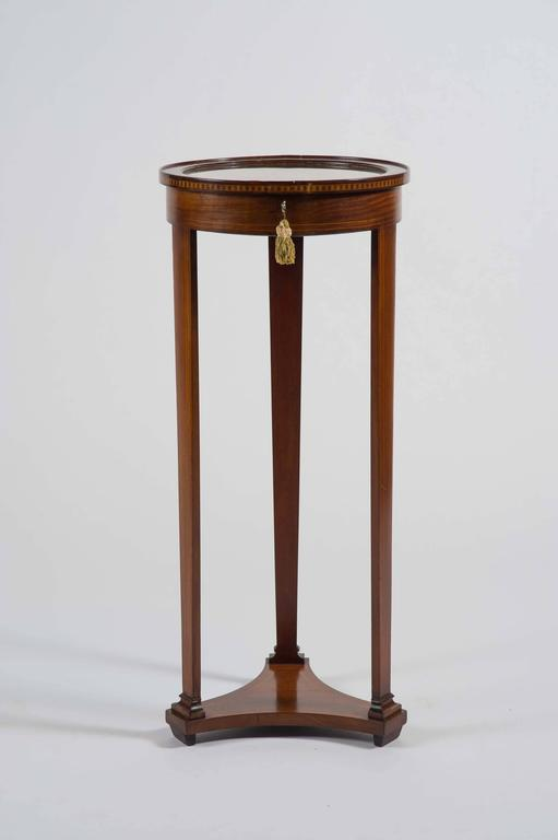 This delightful Edwardian table of mahogany with box wood stringing and inlay throughout of circular form, on three pillar legs and platform base. Lined with gold velvet, with working lock and key. Ideal for a watch, jewelry or cufflink collection.