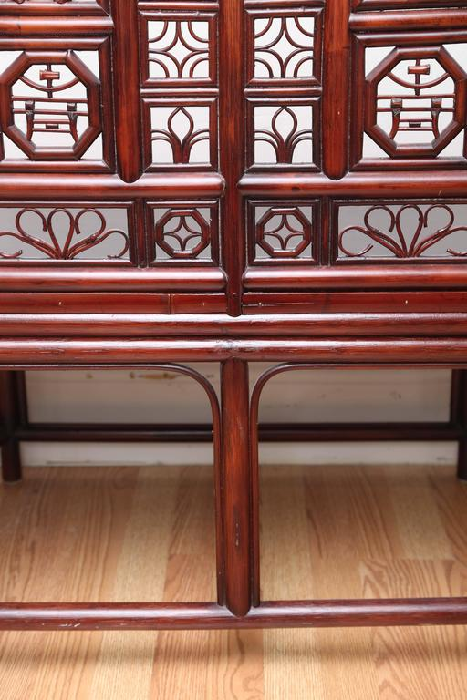 Charming pagoda style Asian loveseat with beautiful fretwork back and sides.