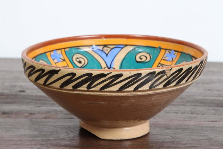 An under-glazed painted pottery bowl with abstract naive design, blue, ochre, brown. Moroccan pottery bowl of deep rounded form with flattened rim rising on a low foot, hand-painted on the exterior with black decoration, the interior in polychrome