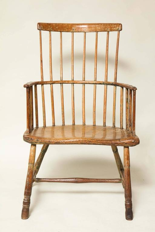 Very good 18th century English comb back Windsor armchair, the simple back supported by eight spindles, the bentwood arm with shaped end supports, over