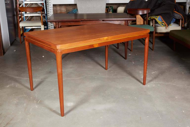 "Mid Century 1950s Teak Expandable Dining Table by Johannes Andersen  This vintage dining table is in excellent condition. This table is in the traditional Danish ""pull out leaf"" style, but with a twist. Braces pull out from either side and"