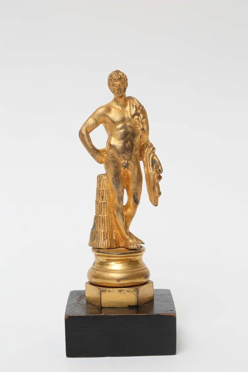 The gilt bronze figure of Antinous is mounted on a circular gilt bronze socle set on an hexagonal gilt bronze plinth attached to a wood base.