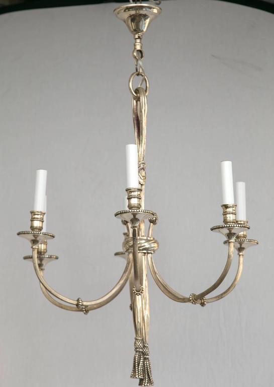 Bronze six-arm chandelier with tassel detail.