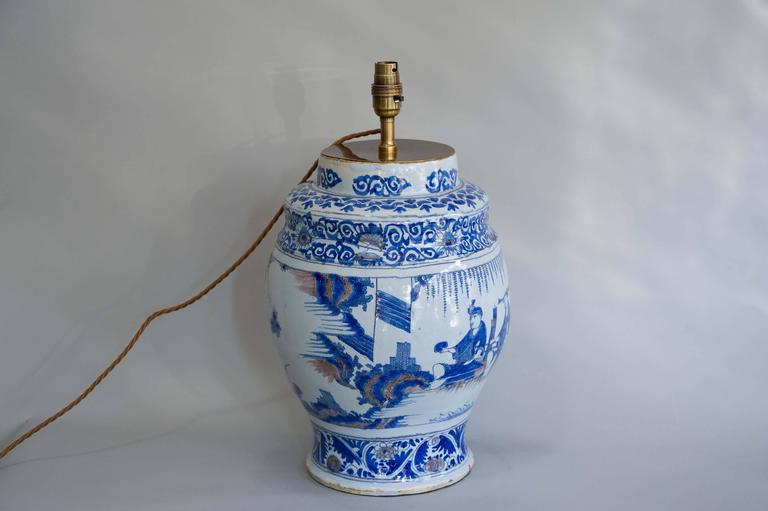 An unusual late 17th century delft blue and white vase with Manganese highlights. The vase itself has an unusual shape and may have been used as a vessel. The decoration shows Oriental figures in various settings and as such can be seen as a type of