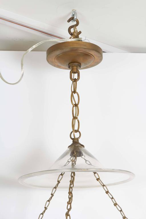 A pair of George III style gilt brass hall lanterns from the George F Baker House, tripartite chain suspending a glass hurricane shade fitted with single Edison socket, circa 1930.