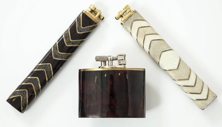 Shagreen lighters with decorative details of black sea shell, both priced at $495 each. Oval lighter made of dark brown sea shell, priced at $495.