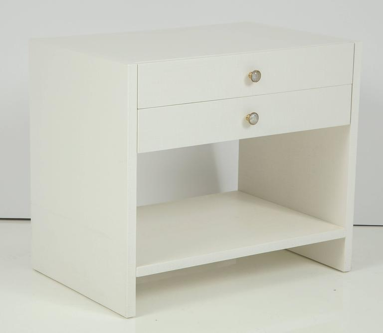 Pair of 1970s custom-made nightstands in off-white lacquered linen and cabachon crysta quartzl and brass knobs. Each nightstand has two pull-out shelves and shelf. Mint restored condition.