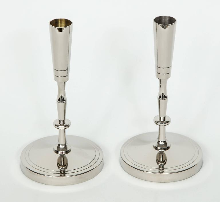 Pair of polished nickel candlesticks with a circular base and sinuous stem designed by Tommi Parzinger for Dorlyn.