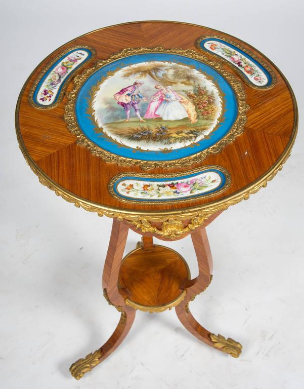 A charming 19th century French kingwood, ormolu-mounted occasional table with inset French 'Sevres' porcelain plaques to the top. The central plaque depicting a romantic scene, the others with flowers all within a turquoise border. Raised on three