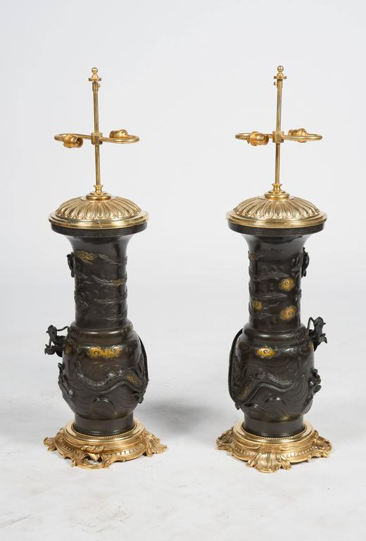 A very impressive pair of 19th century, Japanese, Meiji period (1868-1912) Bronze vases each with mythical dragons wrapped around them, gilded highlights. Mounted in lated gilded ormolu Rococo style bases and tops.