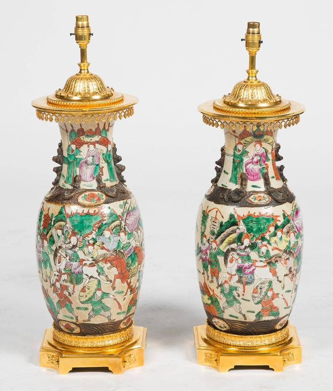 An impressive pair of 19th century Chinese crackleware vases, having classical scenes of warriors on horseback and mounted with gilded French ormolu mounts.