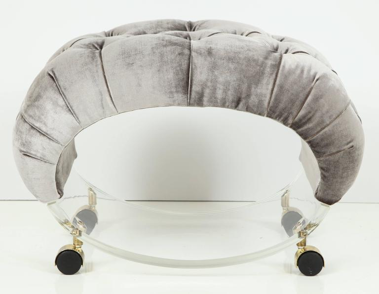This unique sculptural Lucite stool is a jewel. Original brass casters and Lucite is in excellent condition with a few minor scratches from age that cannot even be photographed they are so light and minor. Newly upholstered and tufted in a luscious