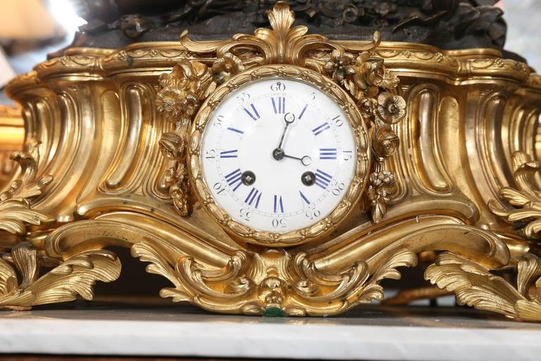 Lovely and large clock depicting a playful putti resting on top of a gilt bronze base. The putti is reaching for a butterfly amidst a group of flowers the clock has a white enamel face with blue numerals. It is in working Order and had the