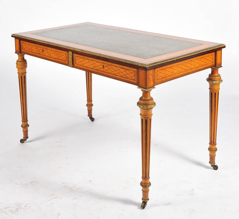 A fine quality satinwood parquetry inlaid library table. Having an inset leather top, gilded ormolu mounts. Two frieze drawers and raised on turned tapering fluted legs, terminating in the original brass castors.