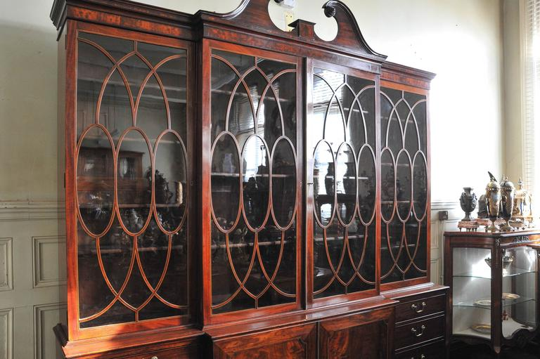 A very good quality late 18th century George III mahogany break fronted Library bookcase. Having a wonderful patina, a swan neck pediment, four glazed doors each with oval astragal inlaid glazing bars. Two central doors with flamed mahogany panels,