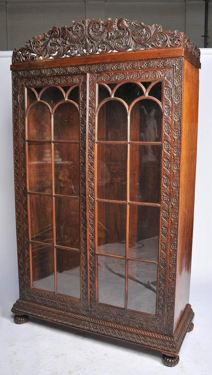 A very impressive 19th century Anglo-Indian display cabinet. Having a wonderful carved and fretted foliate and C scroll decoration. The Gothic influenced glazed doors opening to reveal adjustable shelves and raised on carved bun feet.