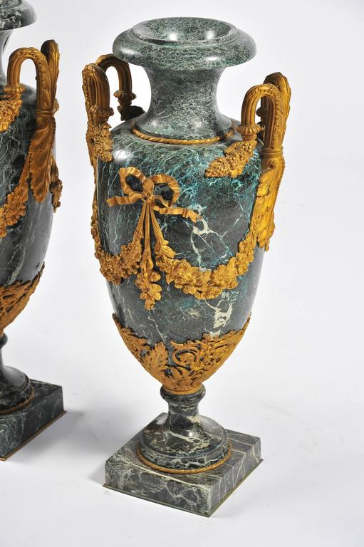 A good quality large pair of Louis XV style green marble urns, having gilded ormolu scrolling handles with foliate and ribbon swags.