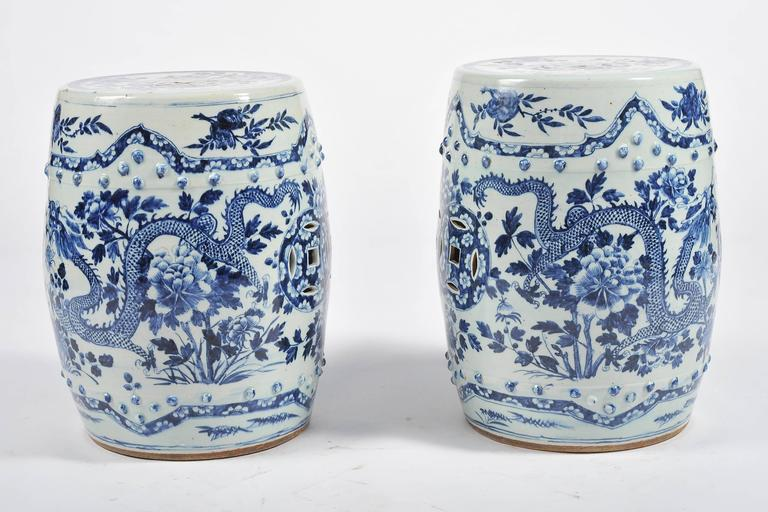 A good quality pair of 19th century Chinese blue and white garden seats. Each having pierced roundels to the top and sides. Mythical dragons painted amongst flowers and foliage.